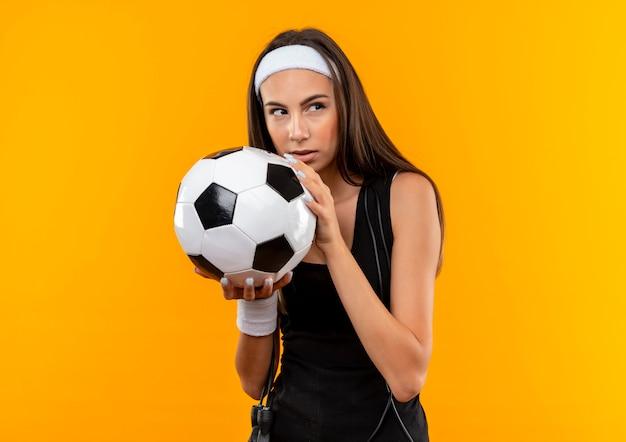オレンジ色の壁に分離された彼女の首の周りに縄跳びで側を見ているサッカー ボールを保持しているヘッドバンドとリストバンドを身に着けている自信のある若いかなりスポーティな女の子