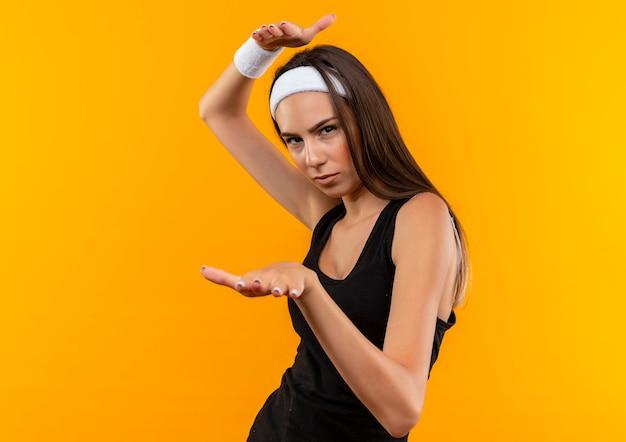 오렌지 벽에 고립 된 크기를 보여주는 머리띠와 팔찌를 입고 자신감 젊은 꽤 스포티 한 소녀