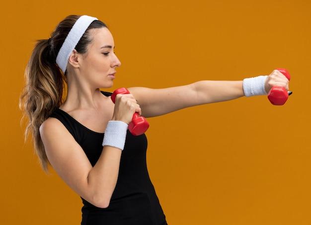 Уверенная молодая симпатичная спортивная девушка с головной повязкой и браслетами, протягивающая гантели, глядя на сторону, изолированную на оранжевой стене