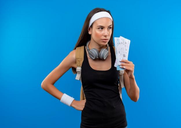 Fiduciosa giovane ragazza abbastanza sportiva che indossa fascia e cinturino e borsa posteriore e cuffie sul collo che tengono i biglietti dell'aereo guardando il lato isolato sulla parete blu