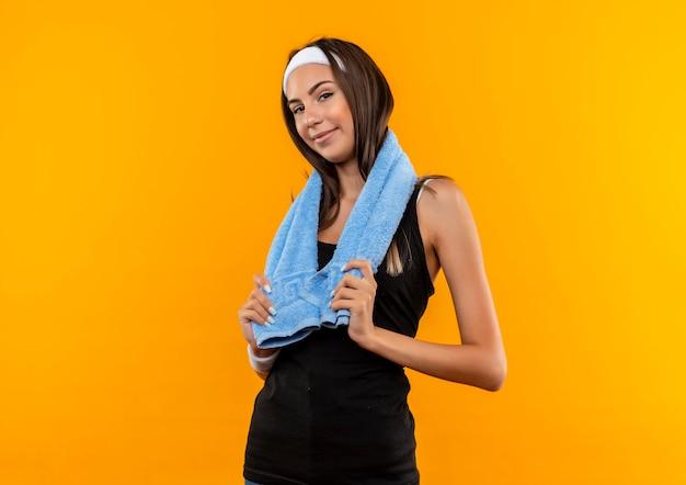 Fiduciosa giovane ragazza abbastanza sportiva che indossa fascia e cinturino che tiene l'asciugamano intorno al collo sulla parete arancione