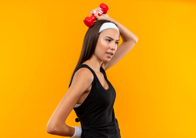 Confident young pretty sporty girl wearing headband and wristband putting dumbbell on head standing in profile view and looking at side isolated on orange wall