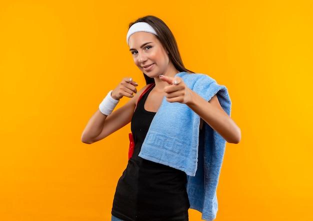 Fiduciosa giovane ragazza abbastanza sportiva che indossa fascia e cinturino con asciugamano e corda per saltare sulle spalle che ti fa un gesto sul muro arancione