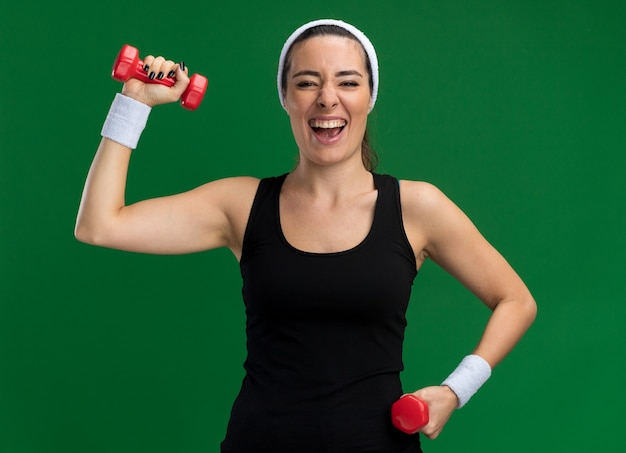 Fiduciosa giovane ragazza abbastanza sportiva che indossa fascia e braccialetti che tengono i manubri isolati sul muro verde