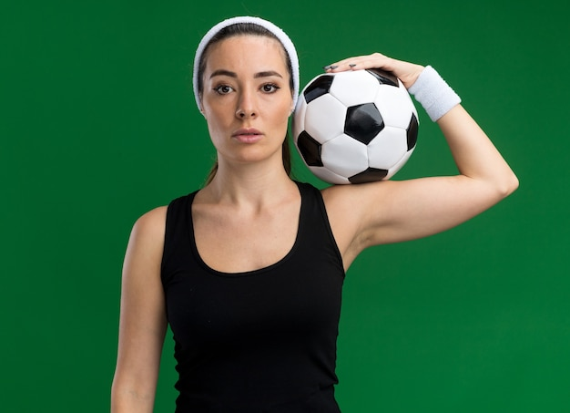 Confident young pretty sporty girl wearing headband and wristbands holding soccer ball on shoulder  isolated on green wall