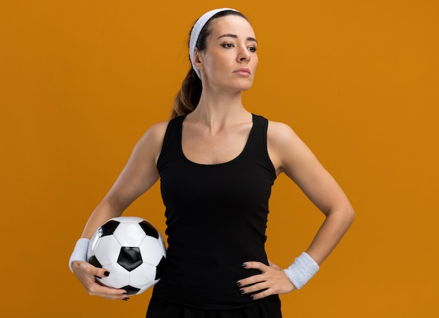 Confident young pretty sporty woman wearing headband and wristbands holding soccer ball keeping hand on waist looking at side