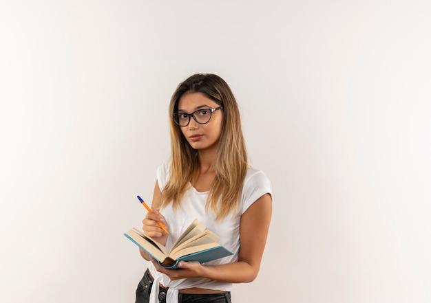 Ragazza graziosa giovane sicura dello studente che tiene penna e libro aperto isolato su bianco con lo spazio della copia