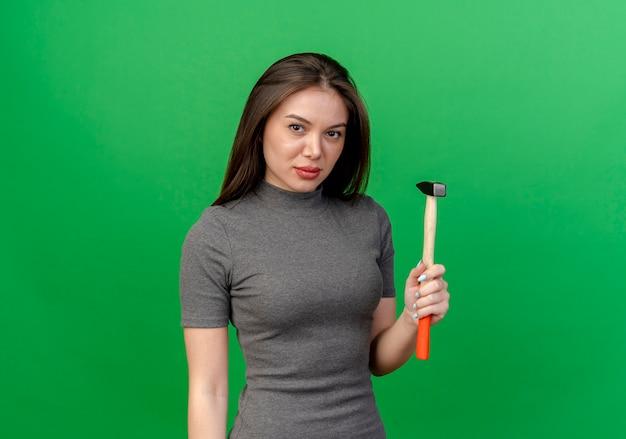 コピースペースと緑の背景に分離されたハンマーを保持している自信を持って若いきれいな女性