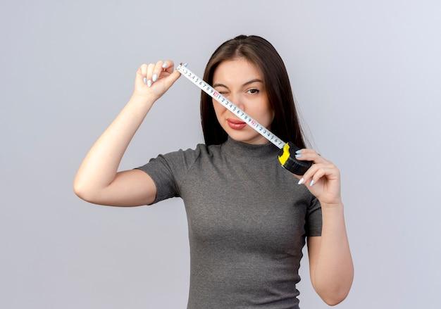 Fiducioso giovane donna graziosa che tiene il metro a nastro che sbatte le palpebre isolato su priorità bassa bianca