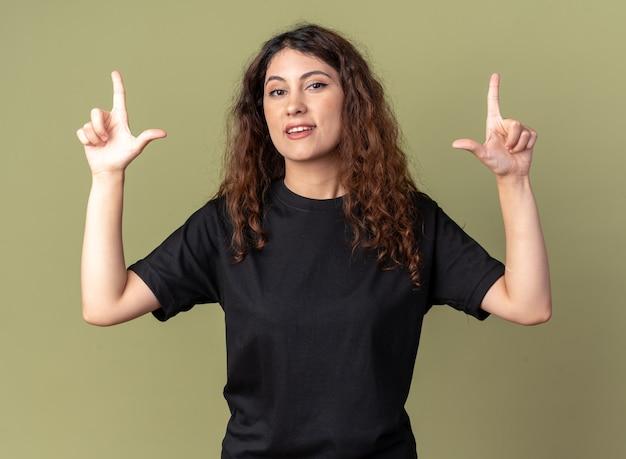 Fiduciosa giovane donna graziosa che guarda davanti facendo il gesto del perdente isolato sul muro verde oliva