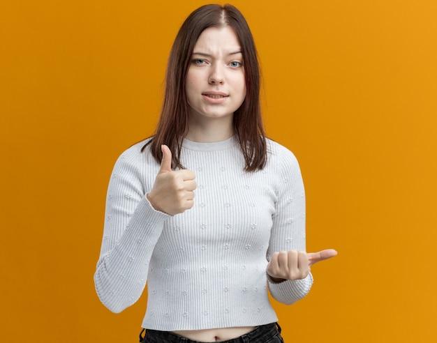 Fiduciosa giovane donna graziosa che guarda davanti mostrando pollice in alto che punta a lato isolato sulla parete arancione con spazio copia