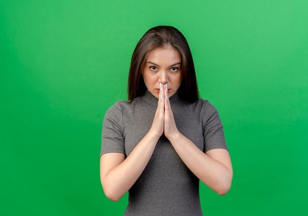 Fiduciosa giovane donna graziosa mettendo le mani insieme sulla bocca guardando la telecamera isolata su sfondo verde con copia spazio