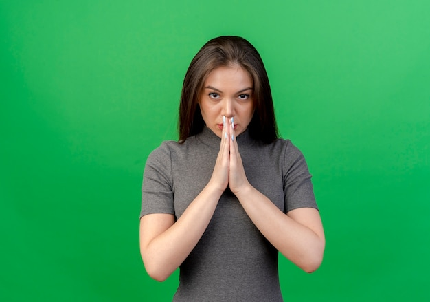 복사 공간이 녹색 배경에 고립 된 카메라를보고 입에 손을 모으고 확신 젊은 예쁜 여자