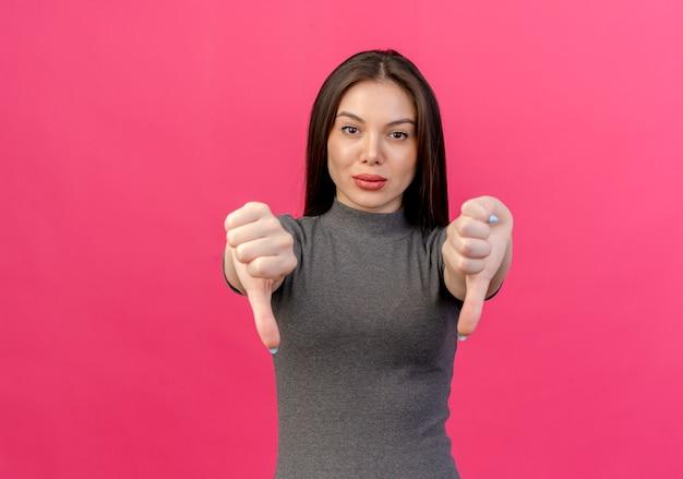 Giovane donna graziosa sicura che mostra i pollici giù isolati su fondo rosa con lo spazio della copia
