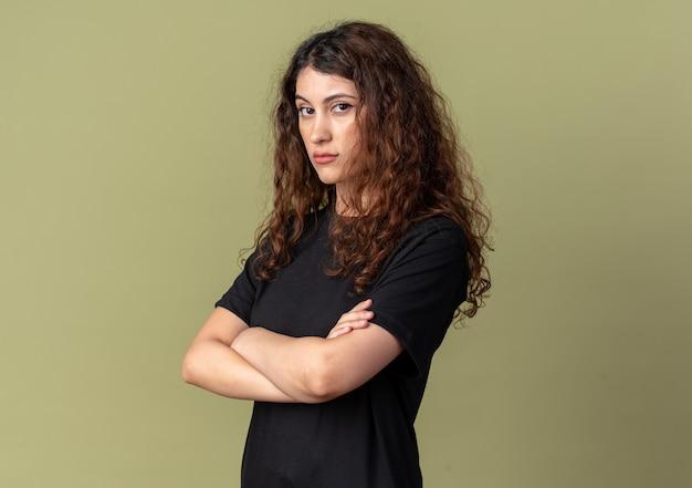 복사 공간이 있는 올리브 녹색 벽에 격리된 전면을 바라보는 닫힌 자세로 프로필 보기에 서 있는 자신감 있는 젊은 예쁜 여성