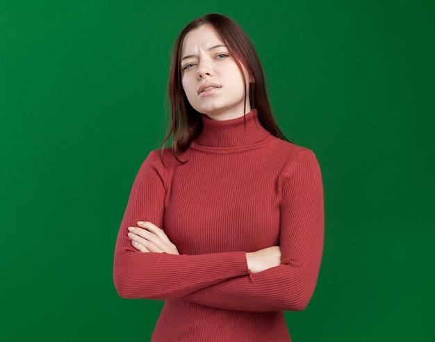 복사 공간이 있는 녹색 벽에 격리된 전면을 바라보는 닫힌 자세로 서 있는 자신감 있는 젊은 예쁜 여성