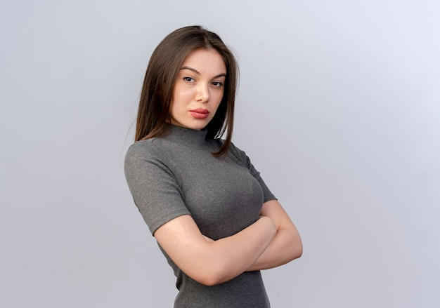 Fiduciosa giovane donna graziosa in piedi con la postura chiusa in vista profilo isolato su sfondo bianco con copia spazio