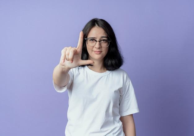 前で敗者のジェスチャーをしている眼鏡をかけている自信を持って若いきれいな女性