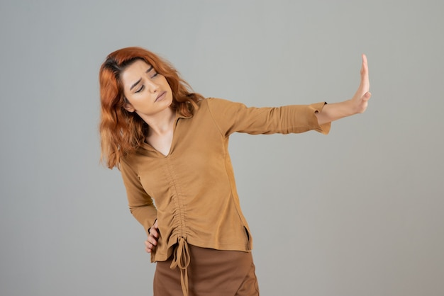 Confident young redhead gesturing stop on grey wall