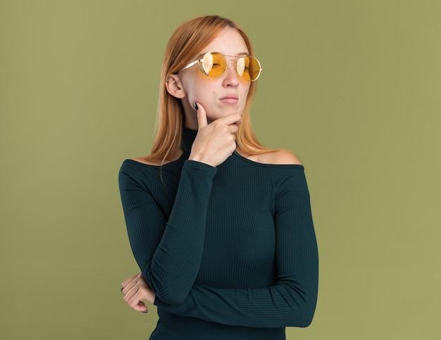 Fiduciosa giovane ragazza rossa allo zenzero con lentiggini in occhiali da sole che tengono il mento e guardano il lato