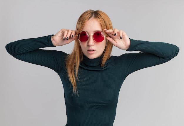 コピースペースと白い壁に分離されたサングラスを通してそばかすと自信を持って若い赤毛生姜の女の子