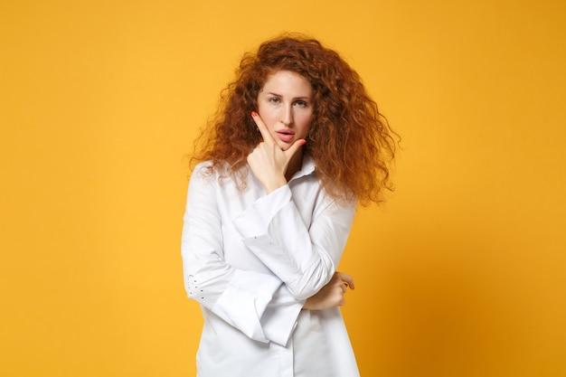 Уверенная молодая рыжая девушка в белой рубашке позирует изолированной на желто-оранжевой стене