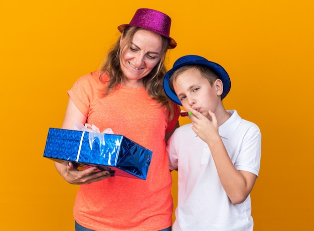 Confident young slavic boy with blue party hat blowing party whistle and standing with his mother wearing violet party hat and holding gift box isolated on orange wall with copy space