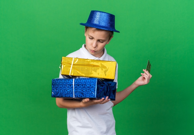 Confident young slavic boy with blue party hat holding credit card and looking at gift boxes isolated on green wall with copy space