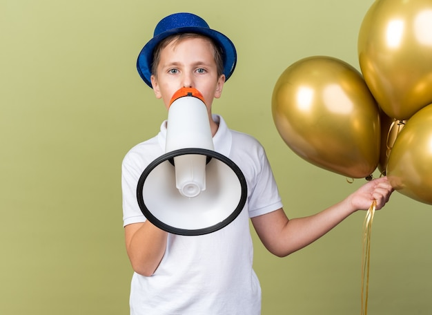 Confident young slavic boy with blue party hat holding helium balloons and talking into loud speaker isolated on olive green wall with copy space