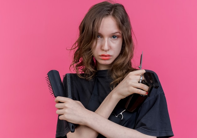 Confident young slavic female barber wearing uniform keeping hands crossed holding spray bottle combs and scissors isolated on pink background