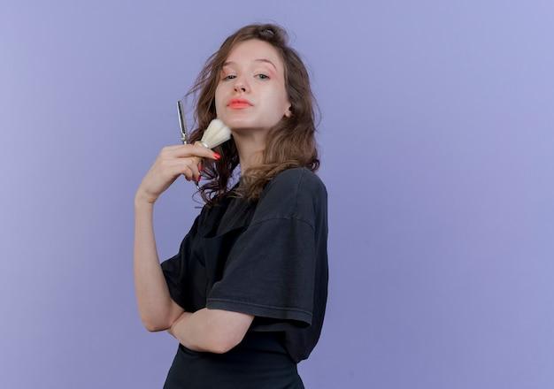 Уверенная молодая славянская женщина-парикмахер в униформе, стоящая в профиле, глядя в камеру, держа ножницы и трогая лицо кистью для бритья, изолированной на фиолетовом фоне с копией пространства