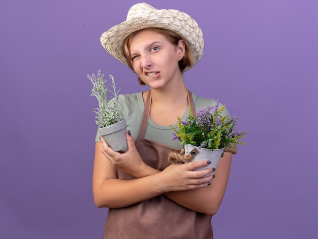 Confident young slavic female gardener wearing gardening hat blinks eye and holds flowers in flowerpots on purple
