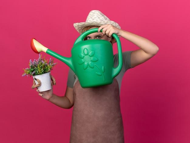Fiducioso giovane femmina slava giardiniere che indossa cappello da giardinaggio guardando la telecamera attraverso l'annaffiatoio e tenendo fiori in vaso