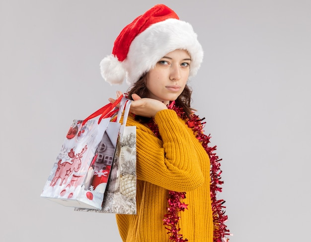 Уверенная молодая славянская девушка в новогодней шапке и с гирляндой на шее держит бумажные подарочные пакеты на плече