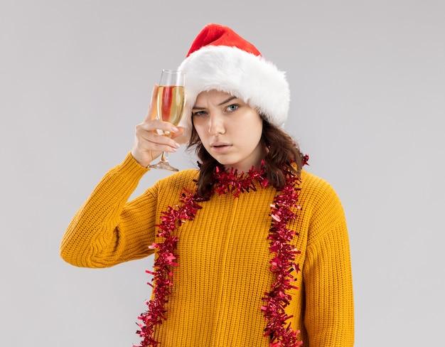 Fiduciosa giovane ragazza slava con cappello santa e con ghirlanda intorno al collo tenendo un bicchiere di champagne isolato su sfondo bianco con spazio di copia