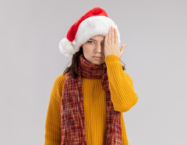 Confident young slavic girl with santa hat and with scarf around neck covers her eye with hand  isolated on white wall with copy space