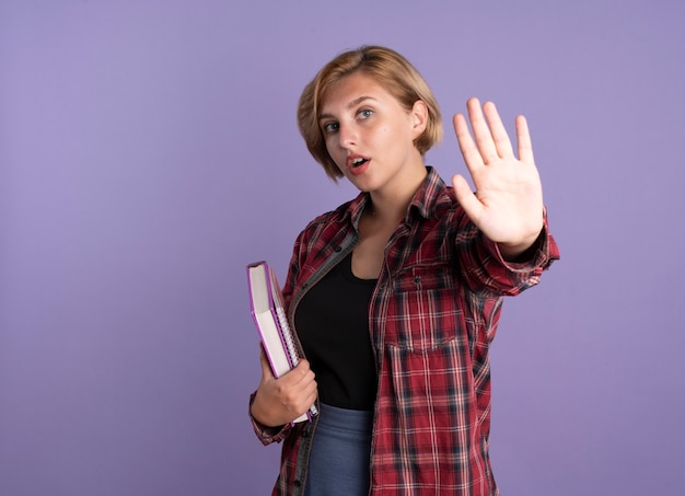 Confident young slavic student girl holds book and notebook gestures stop hand sign