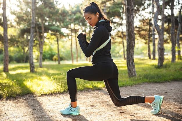 Уверенная молодая спортивная женщина разогревается перед бегом в парке, слушая музыку в беспроводных наушниках