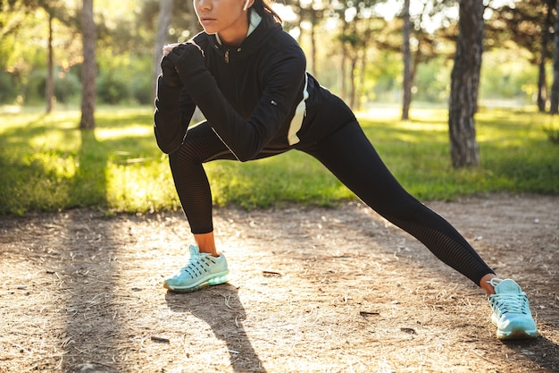 Confident young sports woman warming up before jogging at the park, listening to music with wireless earphones