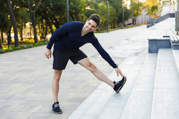 Confident young sportsman doing stretching exercises outdoors