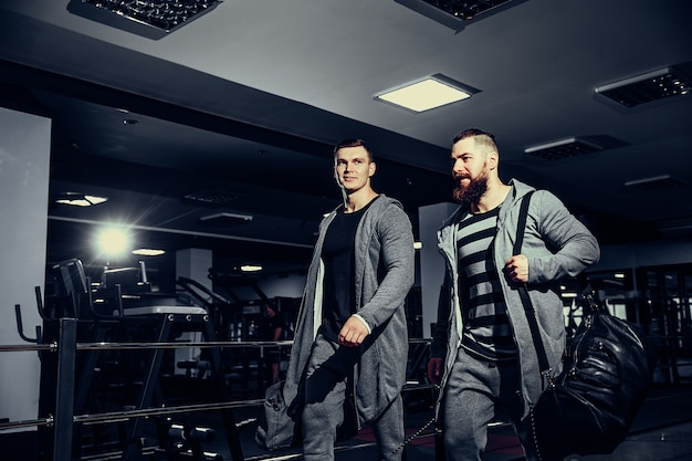 Confident young sportsmen leaving gym