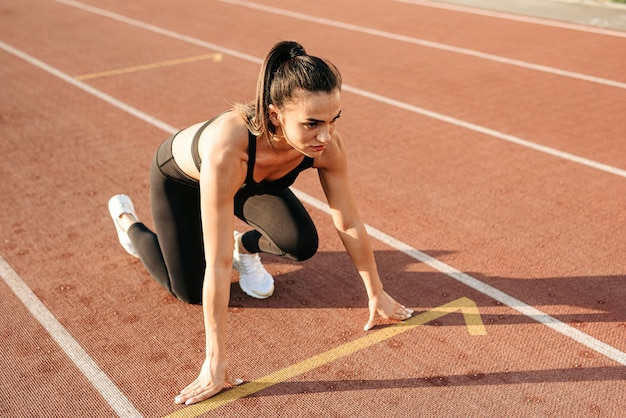 Confident young sportswoman preparing to run the distance in the stadium