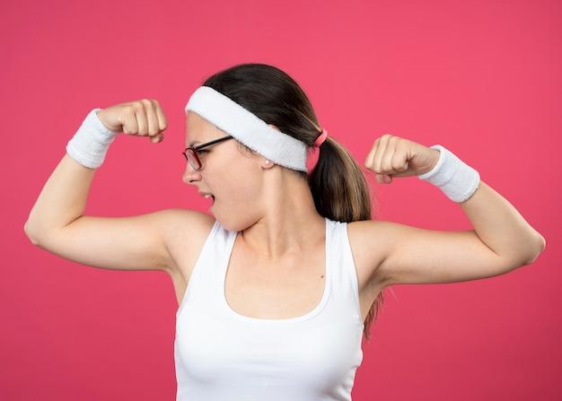 Уверенная молодая спортивная девушка в оптических очках с повязкой на голову и браслетами напрягает бицепсы и смотрит в сторону