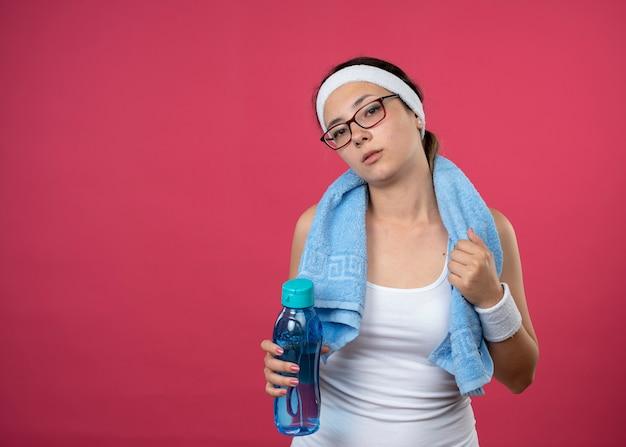 Fiduciosa giovane ragazza sportiva in occhiali ottici con un asciugamano intorno al collo che indossa fascia e braccialetti che tengono una bottiglia d'acqua