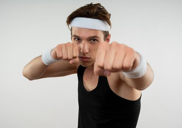 흰색에 고립 된 포즈 싸움에 서있는 머리띠와 팔찌를 입고 자신감 젊은 스포티 한 남자