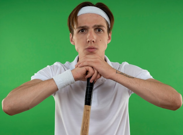 Confident young sporty guy wearing headband with wristband holding baseball bat isolated on green wall