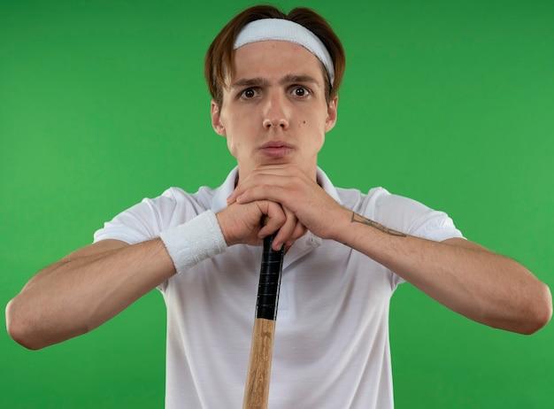 녹색 벽에 고립 된 야구 방망이를 들고 팔찌와 머리띠를 착용하는 자신감이 젊은 스포티 한 남자