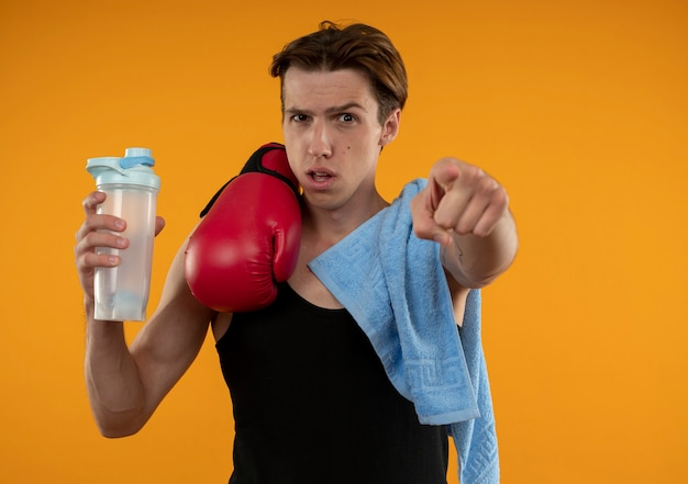 Confident young sporty guy with towel and boxing gloves on shoulder holding water bottle and showing you gesture isolated on orange wall