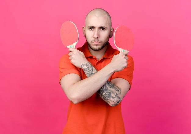 Уверенный молодой спортивный мужчина держит и пересекает ракетку для пинг-понга, изолированную на розовой стене