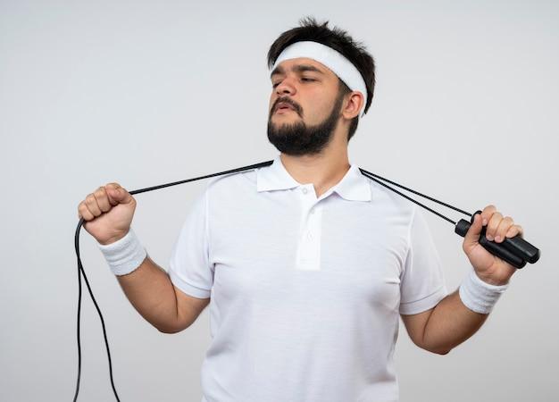 흰 벽에 고립 된 목 뒤에 머리띠와 손목 밴드를 들고 측면을보고 자신감이 젊은 스포티 한 남자